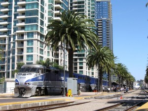 Amtrak train alongside palm trees and high-rise condos.