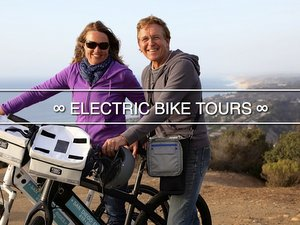 Electric bike tour guests on hilltop overlooking Pacific Ocean